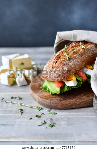 sandwich with avocado and salmon, sandwich with egg, cereal baguette and lettuce leaves on a wooden plate. wooden table and dark background, selective focus and copy space