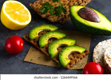 Сrisp sandwich with avocado. Snack Bread and fiber food. Rye, wheat crisp bread, rice bread and lemon, parsley, cherry tomatoes on a dark background. Flat lay