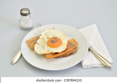 sandwich with bacon and fried egg with salt and pepper on white plate, closeup, isolated on white background