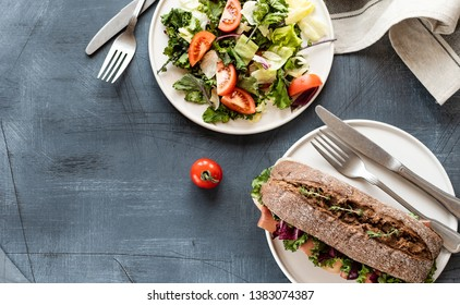 sandwich with baguette , ham, lettuce, kale on gray background, salad from kale and lettuce leaves and tomatoes on a white plate. healthy diet lunch, takeaway sandwich, selective focus, copy space