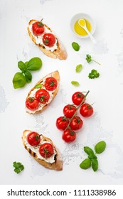 Sandwich with baked cherry tomatoes, garlic, olive oil and curd cheese on white background. Italian Cuisine. Top view.