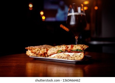 Sandwich in a bar on a wooden table. A tulip glass of beer on the background