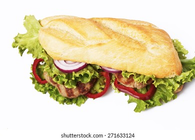 Sandwich with beef cutlet, lettuce, onions and tomato in bun