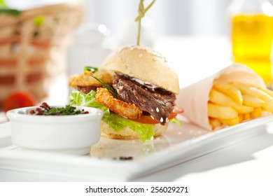 Sandwich with Beef and Deep Fried Onions Ring, Tomato and Cucumber. Garnished with French Fries