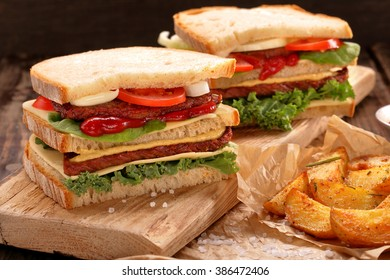 Sandwich with beef, vegetables and baked potatoes on wooden table