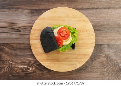 Sandwich bread made of charcoal with melting Cheese, Ham, Tomato, Salad, Onion on a wooden chopping board. Top View.