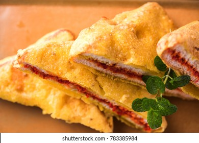 Sandwich Bread Pakora / pakoda (Triangle shape) served  with tomato ketchup, chutney, green chilli  and onion slices, Popular indian  tea-time snack. Selective focus
