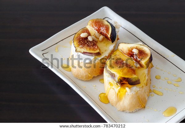Sandwich Bruschetta with Fig, Goat Cheese and Honey. Dark wooden background. Selective focus. Close up.