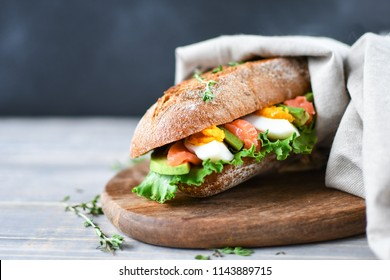 sandwich from a cereal baguette with avocado, salmon, egg and lettuce leaves on a wooden plate. wooden table and dark background, selective focus and copy space