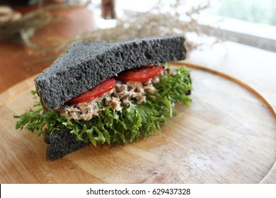 Sandwich charcoal with red fresh tomato, tuna and green vegetables. Black food. Breakfast. Healthy food. On wooden plate.