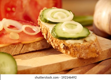 sandwich with cheese, tomato and cucumber slices on wooden table