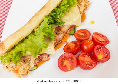 Sandwich with chicken and bacon. Carrot, corn, cucumber and cherry tomatoes