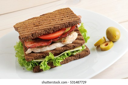 sandwich with chicken and bacon on plate on wooden background