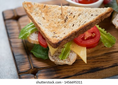 Sandwich with chicken, cheese, salad leaves and tomatoes on a wooden serving board, close-up, studio shot