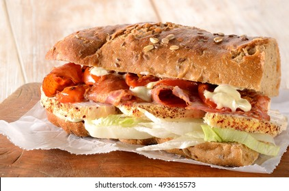 Sandwich. Chicken fillet submarine sandwich with bacon, lettuce and tomato on crusty French bread baguette. Rustic wooden bread board.