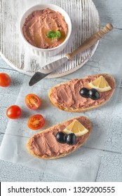 Sandwich with chicken liver pate and black olives on the white parchment