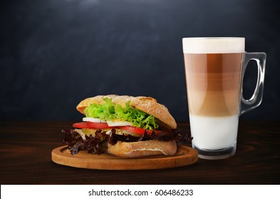 Sandwich with coffee on wooden table