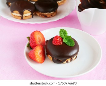 Sandwich cookies with chocolate glaze and strawberries on plate over pink background