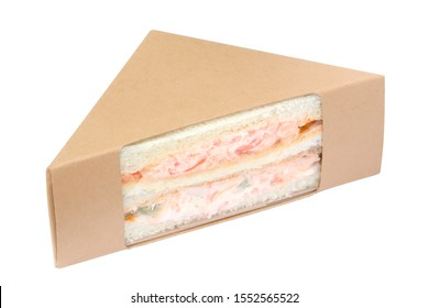 Sandwich with crab stick in brown cardboard triangle packaging isolated on white background