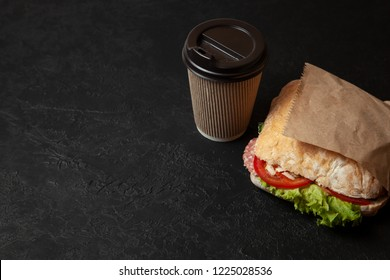 Sandwich and cup of coffee on black background. Morning breakfast or snack when hungry. Street food to go. Copy space for text