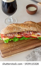 A sandwich of dark bread with salad, bacon, tomatoes and cheese. Breakfast. Fast food