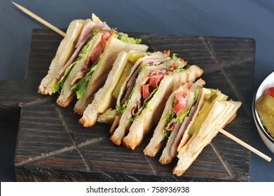 The sandwich is divided into four parts and fixed on a wooden skewer. The filling of the sandwich consists of bacon, cheese and ham. Dark wooden background. Close-up.