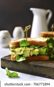 Sandwich with egg avocado salad on a wooden cutting board .Rustic style.