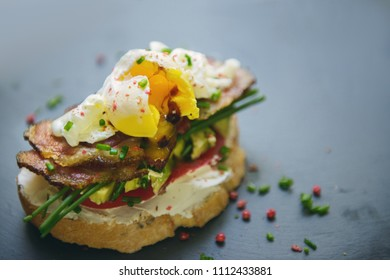 Sandwich with egg poached, bacon and avocado (selective focus)