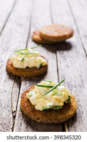 Sandwich with egg salad on a wooden background. Selective focus.