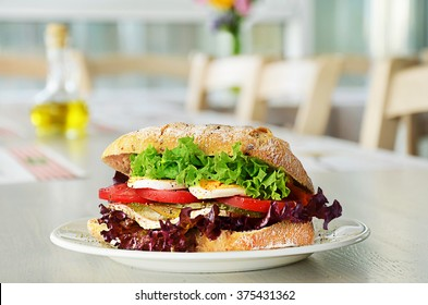 Sandwich with eggs, onion and vegetables on plate