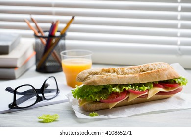 Sandwich from fresh baguette with ham, cheese, salad and tomatoes on work place