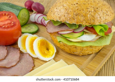 Sandwich, fresh vegetables, cheese, sausage and eggs.