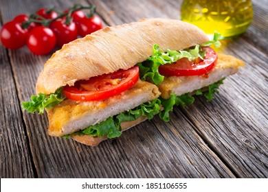 sándwich con pollo frito sobre fondo de madera