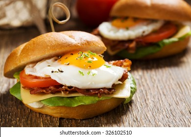 Sandwich with a fried egg, bacon, cheese and vegetables.