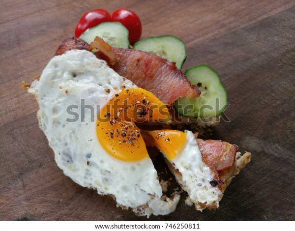 sandwich with Fried egg bacon tyúkember and Cherry tomatoes on wooden board