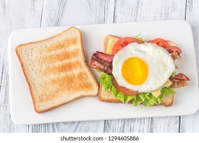 Sandwich with fried egg and bacon on the white plate