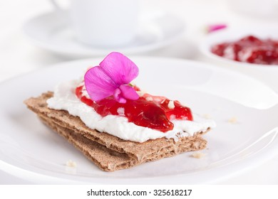 Sandwich with fruit jam and cottage cheese on white plate
