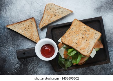 Sandwich with grain bread, salmon fillet, cheese and vegetables on a black wooden serving tray, flatlay over grey stone background
