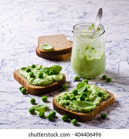Sandwich with green pea puree and basil. Selective focus.