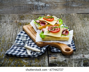Sandwich with ham, cheese, olive oil and tomato on wooden board and on table