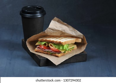 Sandwich with ham and cheese and paper cup with a drink on a dark background. Sandwich in a paper bag. Lettuce and tomato slices are used in the sandwich filling. The concept of fast food. Close-up.