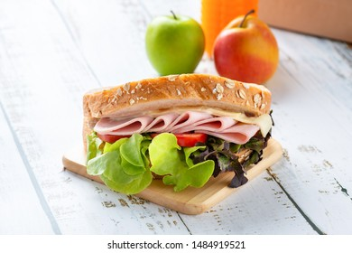 Sandwich ham and cheese, tomato, lettuce with whole grain bread toasted. Orange juice and apple with brown paper lunch.