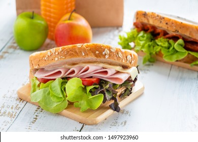 Sandwich ham and cheese, tomato, lettuce with whole grain bread toasted with Salami sandwich. Orange juice and apple with brown paper lunch.
