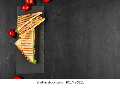 Sandwich with ham, cheese, tomatoes, lettuce, and toasted bread. Top view isolated on black background.