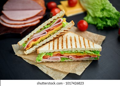 Sandwich with ham, cheese, tomatoes, lettuce, and toasted bread. Above view isolated on black background.
