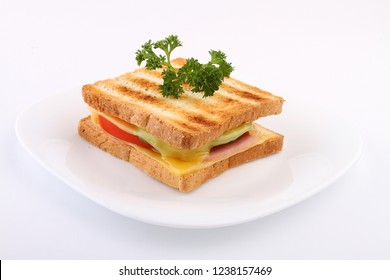 Sandwich with ham, cheese, tomatoes, lettuce, and toasted bread on white background.