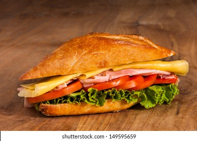 Sandwich with ham, cheese and vegetables on wooden table