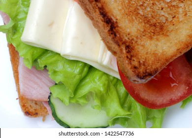 Sandwich with ham, lettuce, slices of cheese, tomatoes, on a white background, bright natural colors.