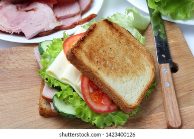 Sandwich with ham, lettuce, slices of cheese, tomatoes, on a cutting board, bright natural colors.