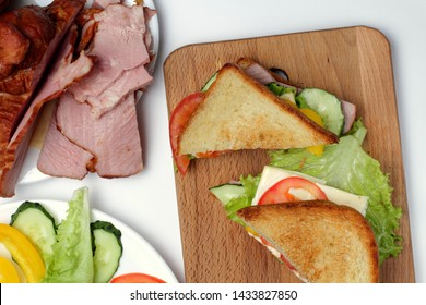 Sandwich with ham, lettuce, slices of cheese, tomatoes, on a cutting board on a white background, bright natural colors.